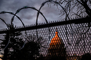 The US Capitol Dome is touched by the rising sun behind security fencing toped with razor wire on Capitol Hill in Washington, DC, on Sunday, January 17, 2021.