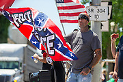 Counter protester Geo Connolly of Lewisburg holds a confederate flag at the corner of 4th and Chestnut Streets during the Mifflinburg Pride Event.