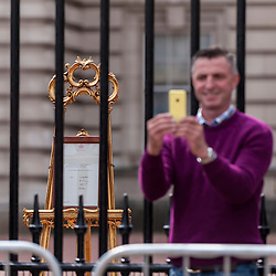 © Licensed to London News Pictures. 02/05/2015. London, UK. A man takes a selfie in front of the royal birth announcement of the Duke and Duchess of Cambridge's second child, a daughter, born at 8.34am, today, 2 May 2015, is posted on an easel outside Buckingham Palace.  The document is signed by the the delivery team at St Mary's Hospital in Paddington - led by Alan Farthing, the royal surgeon-gynaecologist . Photo credit : Stephen Chung/LNP