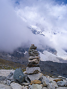 A cairn at Salkantay Pass, giving thanks for making it to this point, along the Camino Salkantay, with Montaña Salkantay and its glacier in the background, near Soraypampa, Peru.