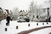 Een vrouw loopt voorzichtig door de sneeuw in Utrecht. In grote delen van Nederland is vandaag voor het eerst sneeuw gevallen
