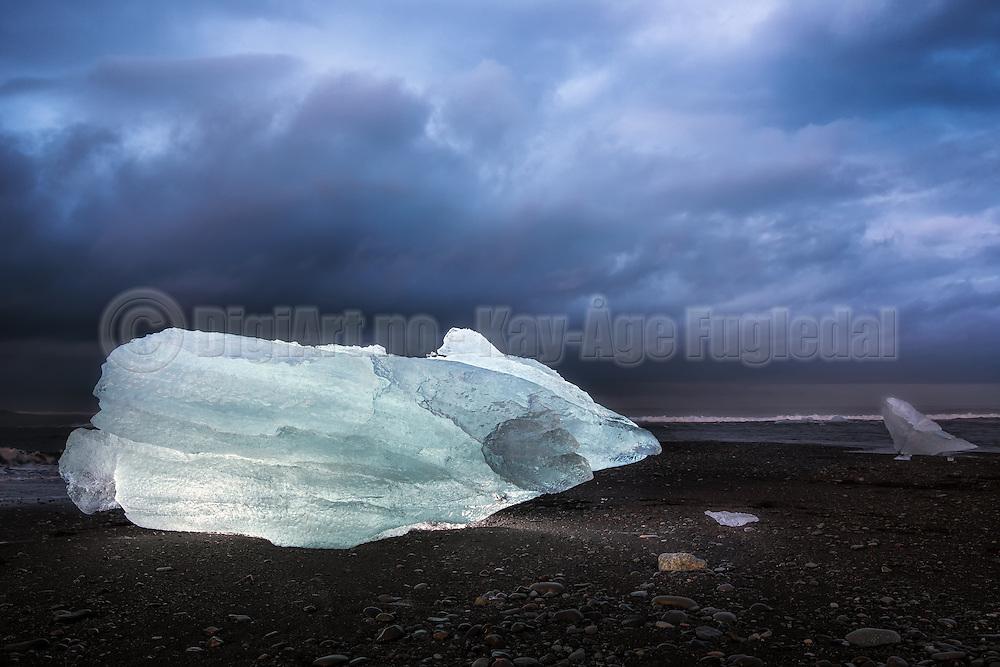Jökulsárlón is the largest ice lake on Iceland, and is located south of the glacier Vatnajökull between Skaftafell nationalpark and Höfn. The lake arised in 1934-1935 and grew from 7,9 km² in 1975 to over 18 km² today, and with a dept of 2oo meters it is the next deepest lake in Iceland. The lump of Ice is backlit with two radio controlled Canon Speedlight flashes   Jökulsárlón er den største bresjøen på Island. Den ligger ved sørenden av isbreen Vatnajökull mellom Skaftafell nasjonalpark og Höfn. Sjøen oppstod først i 1934–1935 og vokste fra 7,9 km² i 1975 til minst 18 km² i dag på grunn av kraftig smelting av isbreen. Med en dybde på om lag 200 meter er Jökulsárlón nå trolig den nest dypeste innsjøen på Island. Isklumpen er belyst med to radiostyrte  Canon Speedlight blitser.