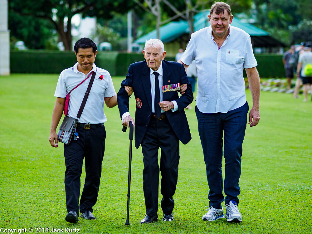 """11 NOVEMBER 2018 - KANCHANABURI, KANCHANABURI, THAILAND: ARCHIE DUNLOP (center), 95 years old, a British veteran of World War II, is helped into the Rememberance Day ceremony at the Kanchanaburi War Cemetery in Kanchanaburi, Thailand. Kanchanaburi is the location of the infamous """"Bridge On the River Kwai"""" and was known for the """"Death Railway"""" built by Japan during World War II using allied, principally British, Australian and Dutch, prisoners of war as slave labor. There are 6,982 people buried in the cemetery, including 5,000 Commonwealth soldiers and 1,800 Dutch soldiers. November 11, 2018 marked the 100th anniversary of the end of World War I, celebrated as Rememberance Day in the UK and the Commonwealth and Veterans' Day in the US.    PHOTO BY JACK KURTZ"""