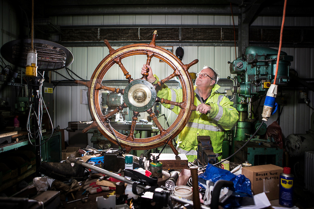 """© Licensed to London News Pictures. 04/05/2016. Birkenhead UK. Picture shows former Tug man & volunteer Phil Janion working on the Daniel Adamson's wheel at the Canada Dock volunteer workshop. The Daniel Adamson steam boat has been bought back to operational service after a £5M restoration. The coal fired steam tug is the last surviving steam powered tug built on the Mersey and is believed to be the oldest operational Mersey built ship in the world. The """"Danny"""" (originally named the Ralph Brocklebank) was built at Camel Laird ship yard in Birkenhead & launched in 1903. She worked the canal's & carried passengers across the Mersey & during WW1 had a stint working for the Royal Navy in Liverpool. The """"Danny"""" was refitted in the 30's in an art deco style. Withdrawn from service in 1984 by 2014 she was due for scrapping until Mersey tug skipper Dan Cross bought her for £1 and the campaign to save her was underway. Photo credit: Andrew McCaren/LNP ** More information available here http://tinyurl.com/jsucxaq **"""