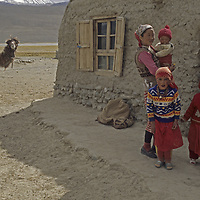 A nomadic Kyrgyz nomad family and one of their camels stand outside their summer hut near Lake Karakul in the  Pamir Mountains of Xinjiang Province of far western China.
