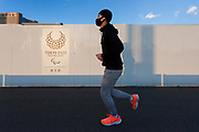 A man, wearing a face mask, runs past a construction site wall with a logo for the 2020 Paralympic games on it Tsukiji, Tokyo, Japan. Wednesday February 3rd 2021 The future of the 2020 Tokyo Olympic and Paralympic  games is still in doubt after being delayed one year due to the COVID-19 pandemic the reschedules dates for the summer of 2021 are looking increasing unlikely as the pandemic continues