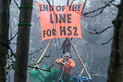 Dan Hooper, better known as roads protester Swampy during the 1990s, occupies a tripod positioned in a misty river Colne in order to try to delay bridge building works in connection with the HS2 high-speed rail link on 7th December 2020 in Denham, United Kingdom. Anti-HS2 activists continue to resist the controversial £106bn rail project from a series of protest camps based along its initial route between London and Birmingham.