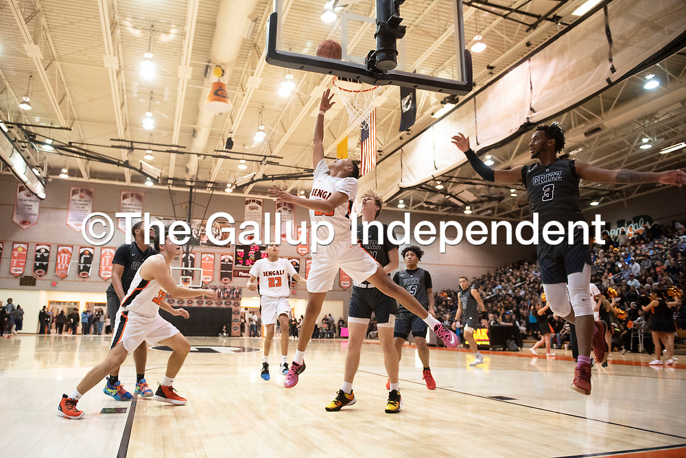 Gallup's Joaquin Ortega (30) drives to the basket for a layup against Spring Valley Saturday night at the Gallup Invitational boys basketball tournament at Gallup High School.