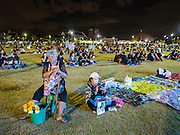 20 OCTOBER 2016 - BANGKOK, THAILAND:  Vendors selling flowers to mourners at Sanam Luang take a break Thursday night. Sanam Luang, the Royal Ceremonial Ground, is packed with people mourning the Monarch's death. The King died Oct. 13, 2016. He was 88. His death came after a period of failing health. Bhumibol Adulyadej was born in Cambridge, MA, on 5 December 1927. He was the ninth monarch of Thailand from the Chakri Dynasty and is also known as Rama IX. He became King on June 9, 1946 and served as King of Thailand for 70 years, 126 days. He was, at the time of his death, the world's longest-serving head of state and the longest-reigning monarch in Thai history.       PHOTO BY JACK KURTZ