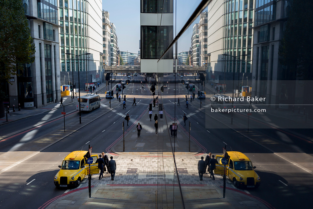 An aerial cityscape of Londoners, general traffic and a London taxi on Upper Thames Street (west of London Bridge) in the City of London - the capital's financial district, on 10th October 2018, in London, England.