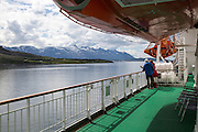 Two people on deck viewing scenery on Hurtigruten ferry ship, near the Arctic Circle crossing, Norway