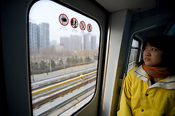 Female passenger travelling on new Airport Express railway between central Beijing and Terminal 2 and 3 at Beijing Airport 2009