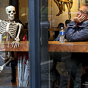 A man takes a break from the rain in Vancouver, British Columbia. The store owner put out the skeleton to attraction attention to this coffee house. (Leica M10 /Summicron 50 mm APO)