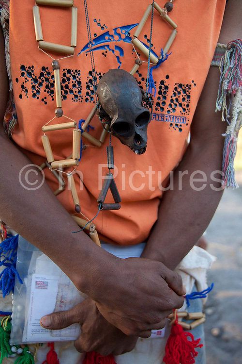 Young Guarani man with a monkey's skull necklace and holding paperwork. The Guarani are one of the most populous indigenous populations in Brazil, but with the least amount of land. They mostly live in the State of Mato Grosso do Sul and Mato Grosso. Their tradtional way of life and ancestral land is increasingly at risk from large scale agribusiness and agriculture. There have been recorded cases and allegations of violence between owners of large farms and the Guarani communities in this region.