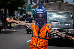 April 18, 2020, Yogyakarta, Indonesia: A traffic control volunteer wears a unique face shield from used water gallon in Yogyakarta, to prevent the spread of coronavirus COVID-19. Indonesian government recommended that people distance themselves from others to slow the spread of the disease of the new coronavirus. Indonesia has so far confirmed 520 deaths, 5.923 positive cases and 607 recovered from coronavirus. (Credit Image: © Rizqullah Hamiid/NurPhoto via ZUMA Press)