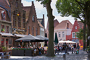 Diners eating out al fresco at restaurants and cafes in Walplein cobbled square in Bruges,  Belgium