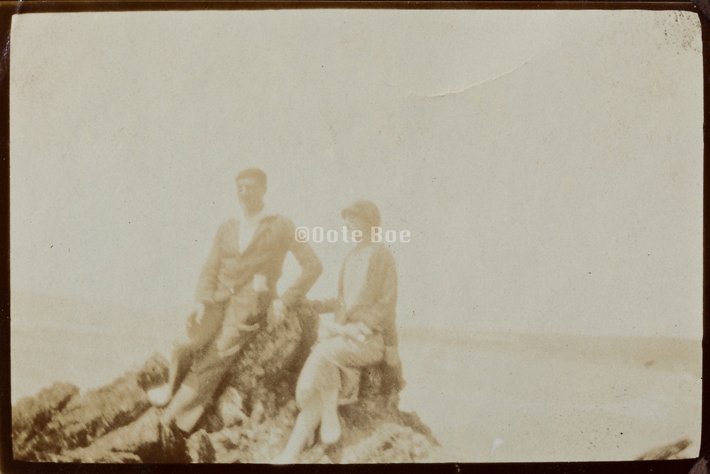 two people posing on top of a rock during a hiking trip 1920s