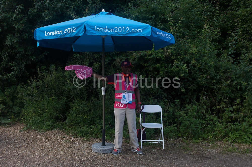 A volunteer directs spectators before the start of the canoe slalom heats at the Lee Valley White Water Centre, north east London, on day 3 of the London 2012 Olympic Games. London 2012 volunteers are called 'Games Makers', as they are helping to make the Games happen. Up to 70,000 Games Makers take on a wide variety of roles across the venues: from welcoming visitors; to transporting athletes; to helping out behind the scenes in the Technology team to make sure the results get displayed as quickly and accurately as possible. Games Makers come from a diverse range of communities and backgrounds, from across the UK and abroad. The vast majority are giving up at least 10 days to volunteer during the Games.