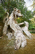 Statue of a dragon, representing wisdom,  fighting a dog and wolf, commissioned by Piaer Francesco Orsini c. 1513-84, The Renaissance Mannerist statues of the Park of Monsters or The Sacred Wood of Bamarzo, Italy .<br /> <br /> Visit our ITALY HISTORIC PLACES PHOTO COLLECTION for more   photos of Italy to download or buy as prints https://funkystock.photoshelter.com/gallery-collection/2b-Pictures-Images-of-Italy-Photos-of-Italian-Historic-Landmark-Sites/C0000qxA2zGFjd_k .<br /> <br /> Visit our EARLY MODERN ERA HISTORICAL PLACES PHOTO COLLECTIONS for more photos to buy as wall art prints https://funkystock.photoshelter.com/gallery-collection/Modern-Era-Historic-Places-Art-Artefact-Antiquities-Picture-Images-of/C00002pOjgcLacqI