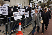 English couple pass Islamic extremists protest at London Libyan embassy and demand Shariah law after the Gaddafi uprising. Holding up their placards that ask for Shariah law for Libya and that Democracy is the path to Hellfire, the young British radicals stand behind barriers near Hyde Park Corner denouncing Colonel Gaddafi and for their views and ideology to become the way of life for the north African country.
