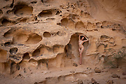 Nude woman standing in a crevice of Crack Canyon, San Rafael Reef, Utah