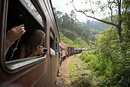 On the train to Ella, Sri Lanka, a young woman holding a camera looks out the window at the scenic landscape. (April 9, 2017)
