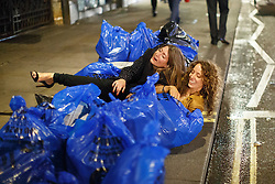 "© licensed to London News Pictures. London, UK 14/12/2013. ""Mad Friday"" revellers fall on some bin bags in Soho, London whilst enjoying the last Friday night out before Christmas, which is also the busiest night of the year for emergency services. Photo credit: Tolga Akmen/LNP"