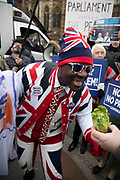Leave means leave pro Brexit anti Europe demonstrator wearing patrioric Union Jack flags is goaded with a lettuce, a comment on European imported food, in Westminster opposite Parliament on the day MPs vote on EU withdrawal deal amendments on 29th January 2019 in London, England, United Kingdom.