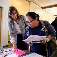Charlene Mitchell, center, a University of New Mexico-Gallup (UNM-Gallup) student and Tracy Lassiter, Assistant Professor of English and Gallup Chapter President for American Association of University Women view flyers at a forum on Native Women's Equal Pay Day Thursday, Sept. 27, 2018 at UNM-Gallup.