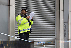 © Licensed to London News Pictures. 02/04/2018. London, UK. Police at the crime scene next to a parade of shops on the A12 in Bromley by Bow, E3 where a teenager was stabbed last night at around 6:05pm. A 16 year old boy suffering stabbing injuries and also a further victim were taken to an east London hospital by London Ambulance staff. The teenage victim remains in a critical condition this morning. Photo credit: Vickie Flores/LNP