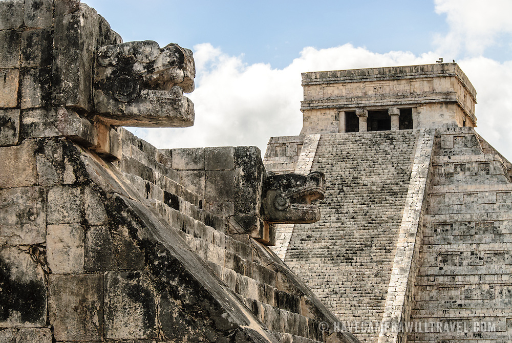 In the background at right is the Temple of Kukulkan (El Castillo) and at left in the foreground are two carved jaguar heads of the Venus Platform at Chichen Itza Archeological Zone, ruins of a major Maya civilization city in the heart of Mexico's Yucatan Peninsula.