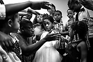Members of the New Life Tabernacle congregation pray over Josnika Adult, 5, on October 22, 2017, in Belle Glade, Florida. They called up God the Father to heal Josnika of her kidney cancer, which she was diagnosed with when she was three years old. (photo by Calla Kessler/The Palm Beach Post)