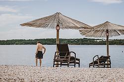 THEMENBILD - ein Mann am Strand mit Sonnenschirm und Liegestühle, aufgenommen am 04. Juli 2020 in Novigrad, Kroatien // a man on the beach with umbrella and sun chairs in Novigrad, Croatia on 2020/07/04. EXPA Pictures © 2020, PhotoCredit: EXPA/ JFK