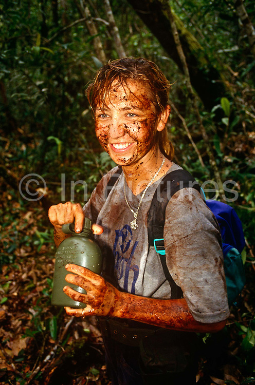 A young girl volunteer is caked in mud after an activity on a Raleigh International expedition in the rainforests of Brunei, Borneo. Beaming from ear to ear, the lady relishes her time here in one of the remotest and most dangerous habitats on the planet. It will have been a life-changing experience for her and her newfound friends from all over the world who will have had to raise several thousands of sponsored Pounds for the privilege of spending two months away from a dull, comfortable life at home, rather than building community projects like bridges or schools. Raleigh International is a charity that provides adventurous and challenging expeditions for people from all backgrounds, nationalities and ages, especially young people. Over the last 23 years, 30,000 people have been involved in more than 250 expeditions to over 40 countries.
