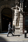 A businessman walks past an Atlantes figure by the sculptor H.A. Pegram (1896) at the entrance of Drapers' Hall livery company in Throgmorton Street, on 17th Juy 2017, in the City of London, England. The Drapers' Company is a Livery Company in the City of London whose roots go back to the 13th century, when as its name indicates, it was involved in the drapery trade. While it is no longer involved in the trade, the Company has evolved acquiring a new relevance. Its main role today is to be the trustee of the charitable trusts that have been left in its care over the centuries. The Company also manages a thriving hospitality business. The first Drapers' Hall was built in the 15th century in St Swithin's Lane.  It bought a Hall on the present site in Throgmorton Street in 1543 from King Henry VIII for £1,200 (about £350,000 in today's money). The Hall that the Company purchased from King Henry VIII in 1543 had been the private residence of Thomas Cromwell, Earl of Essex until his execution in 1540, when it was confiscated by the Crown.