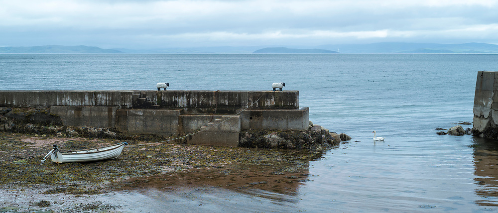 Rowing boat tied to a sheep bollard and moored on the seashore in dock near Corrie on the Isle of Arran, Scotland