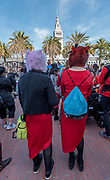 """Two women wear """"pussy hats"""" of fur with red dresses while standing in Justin Herman Plaza for the International Women's Day rally before the march."""