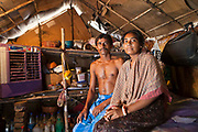 A husband and wife sit in their home in Tehkand Slum, Delhi , India.  The house structure is made from wooden sticks and cardboard.  Indian slums are characterized as a run-down area of a city with substandard housing, squalor and lacking in security.  They are home to increasing numbers of people and families who are usually very poor or socially disadvantaged. Most slums lack clean water, sanitation and other basic services, and as such they pose a serious threat to public health as infectious diseases are able to spread easily, such as Tuberculosis (TB) and cholera.