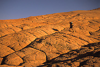 A young man hikes on slickrock in the  Grand Staircase-Escalante National Monument, Utah.