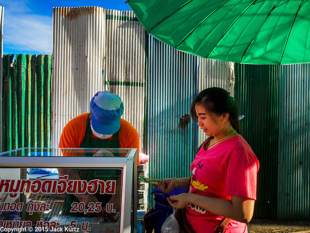 29 JUNE 2015 - BANGKOK, THAILAND: A woman buys a snack of fried chicken feet from a vendor who set up in front of the construction fence around the old Bang Chak Market. The Bang Chak Market serves the community around Sois 91-97 on Sukhumvit Road in the Bangkok suburbs. About half of the market has been torn down, vendors in the remaining part of the market said they expect to be evicted by the end of the year. The old market, and many of the small working class shophouses and apartments near the market are being being torn down. People who live in the area said condominiums are being built on the land.     PHOTO BY JACK KURTZ