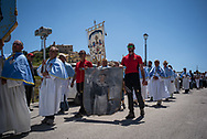 About ten month after the event villagers have been able to organize a mass and a religius procession to celebrate the patron saint, Saint Vincenzo. Member of the mountain rescue team holding the arazzi representing the saint they have rescued from the church rumbles