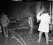 Car Bomb Damage in Dublin (E10)..1972.02.12.1972..12.02.1972..2nd December 1972..On the morning of 2nd December '72 two car bombs exploded in Dublin City. At Sackville Place two busmen were killed as they waited in their car to resume work. The busmen were named as George Bradshaw (30) and Thomas Duffy (23). The bomb was thought to be planted by a Northern Ireland subversive group who hoped to influence legislation going through Dail Eireann in relation to the I.R.A...Picture of the aftermath of the explosion at Liberty Hall, Eden Quay,Dublin. Firemen are seen hosing down the the still smouldering wreckage.
