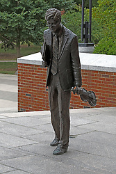 A statue of Minor Myers stands on the landing above the steps just outside of Ames Library on the campus of Illinois Wesleyan University in Bloomington Illinois