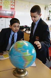 Secondary school students looking at a globe in a geography lesson,