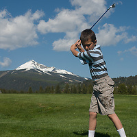 Youngster Eddie Starz swings at Big Sky Golf Course in Big Sky, Montana.