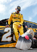 Matt Kenseth has an angle brace adjusted by his three-old-daughter, Clara Mae, before the start of a NASCAR Cup Series auto race at Kansas Speedway in Kansas City, Kan., Sunday, Oct. 22, 2017. (AP Photo/Colin E. Braley)