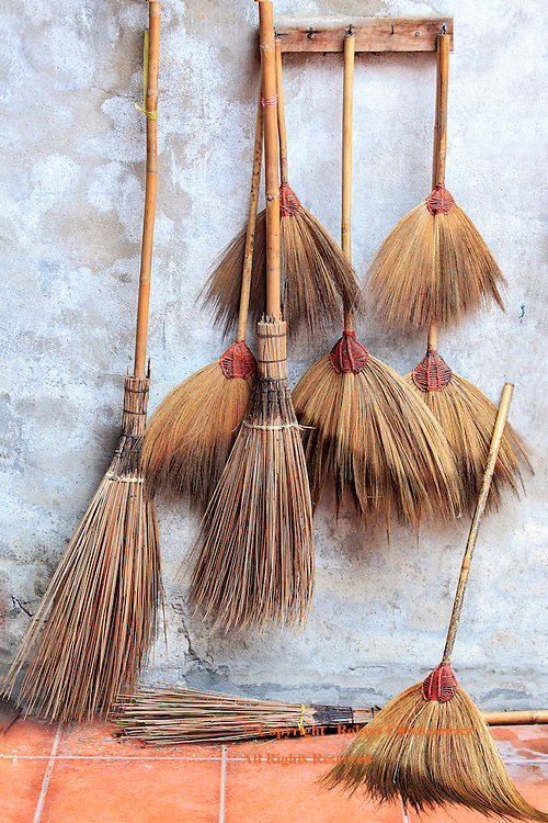 Swept: Numerous hanging and standing straw brooms wait within the monk's residences, in the Buddhist temple of Kuan An Keng Shrine, Bangkok Thailand.