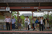 Tourists and commuters wait on the platform at Inari station for a Kyoto bound train.