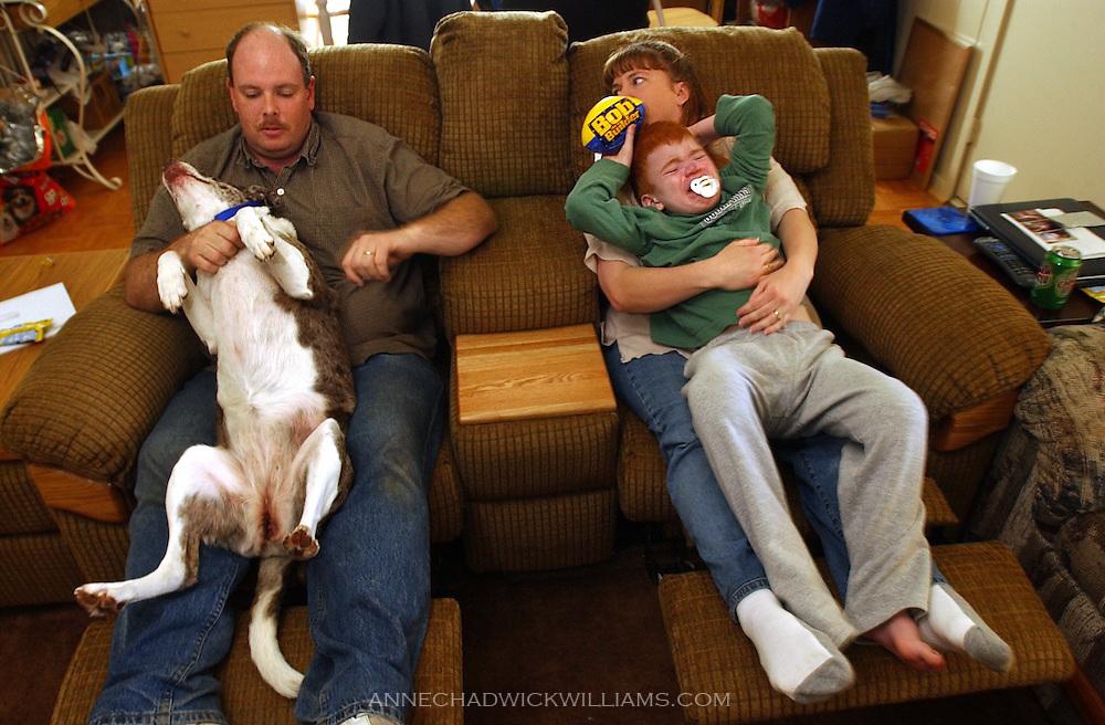 John Bennett scratches the family dog, Smore, as Alicia Bennett comforts son, Hunter. February  23, 2004