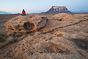 A young man sits enjoying the views surrounding his wilderness campsite on BLM land near Factory Butte, Utah.